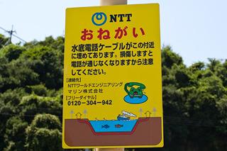 岩黒島で見た看板。よく見かける「ケーブル切られて泣いてる電話キャラ」だが、「水底電話ケーブル」っていうのがすごい。