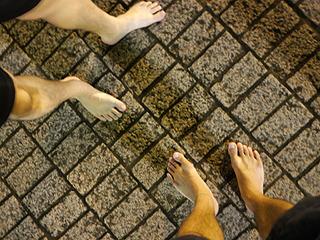 裸足で向き合う男二人。抱き合ってはいない。