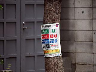 ゴミ出しの説明を街路樹に。もし街路樹に警視庁がなんか貼ったら問題になるのだろう。