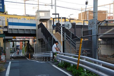 階段の下(画面右下)でこどもと母親が電車を見ている