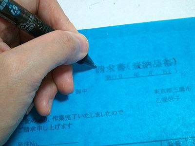 ガリ切り風景。青いシートを元絵の上に載せ、ボールペンでひっかく。