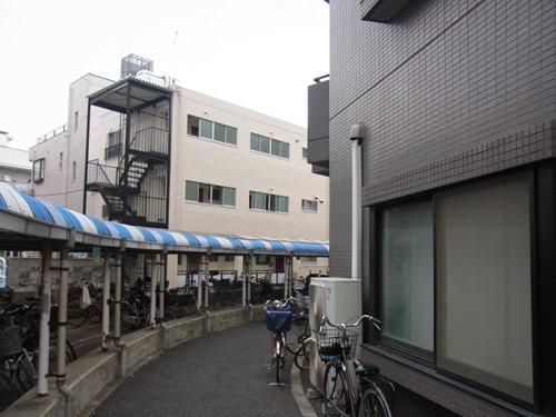 建物が自転車駐車場に背を向けて建っている。