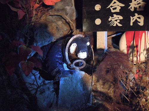 逆パンダのカラーリングをされた木彫りの熊にヘビが絡まってまーす