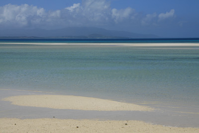 遠浅の海の沖合いに白砂の島が見える
