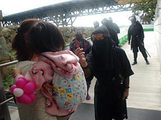 泣いてしまった子供に、しろまるひめのハンコが押された折り紙手裏剣をあげる忍者。目がやさしい。