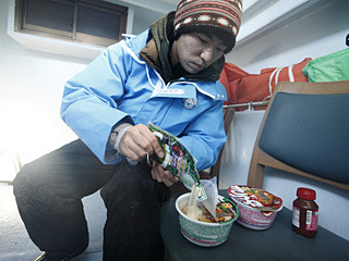揺れる船のキャビンの中でお手軽クッキング。粉末スープとお湯を入れたら、キムチの素かグリーンカレーの素をトッピング。