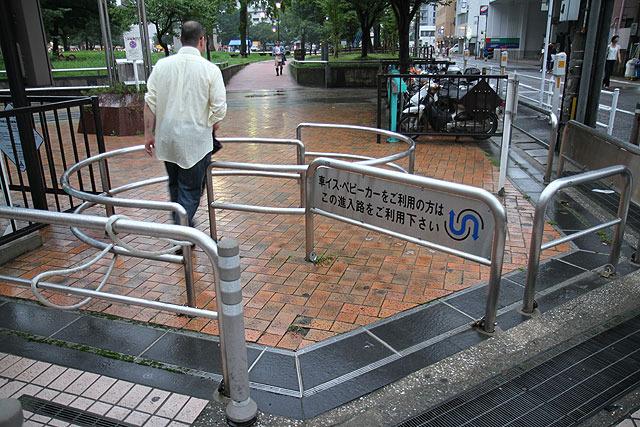 男性が左右にステップを踏みながら公園に入っていく。