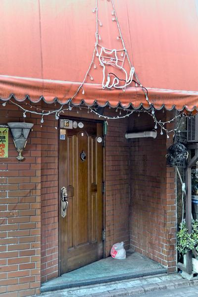 ネコの浮かれ電飾、重厚な扉、そして斜め。あと右側のエアコンのパイプがいったん壁から出てまた入っていっているのがいい。