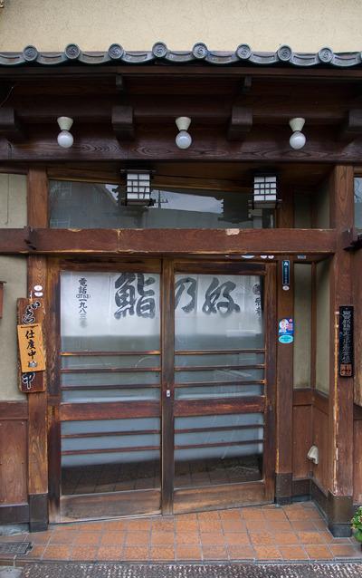 寿司やさんも斜めに!引き戸の事例ははじめてだ。手前の斜めではない梁の存在が、扉の斜め感を際立たせている。名品だ。