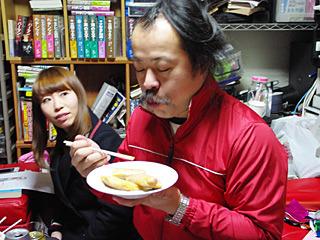 赤飯たらこふりかけ魚肉ソーセージ巻きを食べる宮城さん。隣の『珍しい人をみるような顔』が印象的だ。