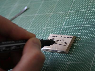 透明なシートを原画にかぶせ、油性マーカーで両面に絵を移す。