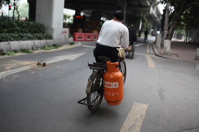 かなり使い込まれた自転車にガスボンベを装着している。無茶だ。重くてバランス悪いのではないか。やはり常に右へ右へと振れていた。