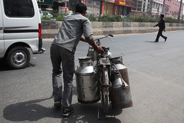 前後左右にミルクを入れたタンクを装備した自転車。ほとんど軽トラ並みの運搬力である。インドの交通量の多い幹線道路をこれが横切る。