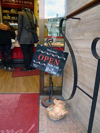 生ハム・サラミ専門店の店頭のカゴの中には、すやすやと眠る子豚。