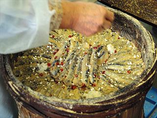 並べたイワシの上に、米麹と唐辛子と糠を振りかけて何層にも重ねていく。