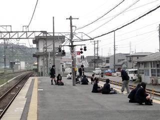 乗換駅では学生がホームに座り