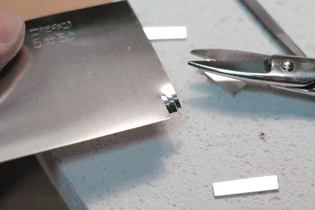 「銀ロウ」という、いわば銀の接着剤みたいなもので台座をくっつける。ごくごくちっちゃく切って使う。くっつけたいもの同士との間に置いてバーナーで熱するとくっつく、という代物。