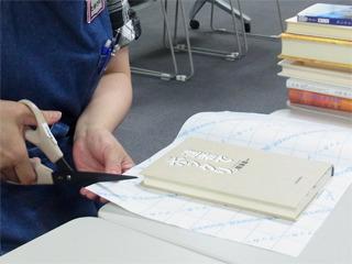 次にシートの上に本を固定して、一回り(5cmくらい)大きめに切ります