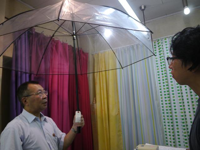 二人が入れる大きい傘はテラボゼン。価格は12,600円で100円傘120本分。