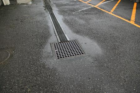 駐車場に降った雨が排水溝の周りに集まる