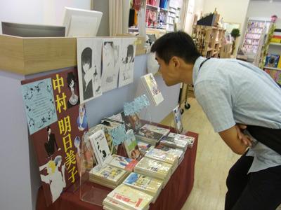 腕を組みながら原画に興味を示す小野さん。近くの古本屋さんの前にこういう人たくさんいる。