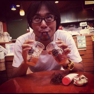 ふざけて二人分飲んでいるカフェデートの写真。実際は一人で二人分を頼んだので、ただ急いで飲んでいるだけ