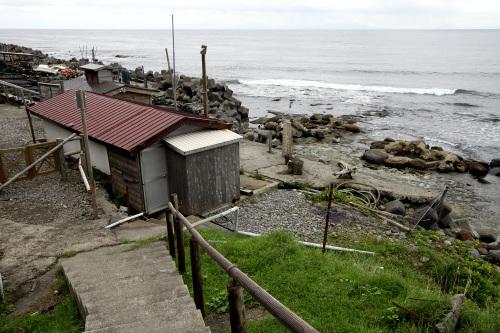 手前に小屋があり、その奥に湯船らしきものが