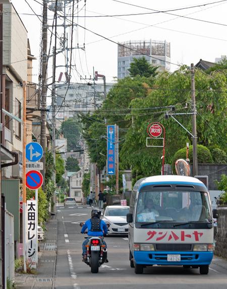 伊東駅を降りて、見れば丘の向こうに「ハト…」の文字が!そして送迎バスもやってきた。この通りを「ハトヤ表参道」と呼ぼう。