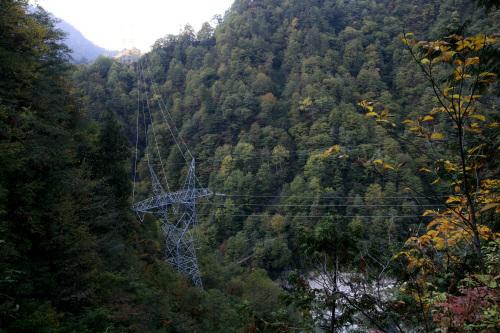 送電線は鉄塔を経由して山の向こうに伸びている