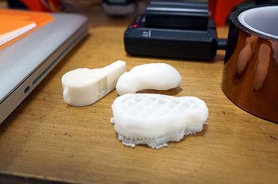 その脇で、机の上には3Dプリンタで作った立体が無造作に置かれていた。もうすぐ僕のティッシュがこの仲間に加わるのだ!