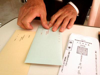 次に、選挙管理委員会の人が内側の封筒を外側の封筒に入れ、封をする。これで投票完了