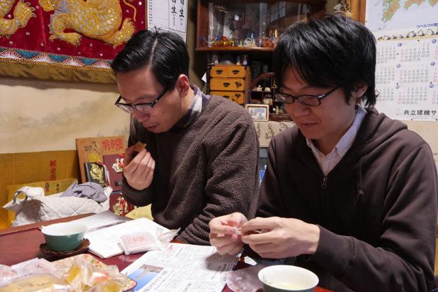 人んちでお茶菓子を食べる筆者(左)とカメラ藤原(右)