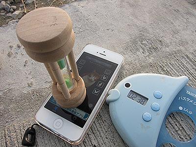 iPhoneがブーン、ブーンと振動してます。その上に砂時計を置きました。