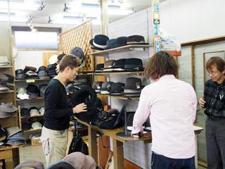 社長にインタビューしているあいだもさりげなく帽子を選ぶ横山さん