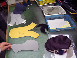 黄色いタコウインナーのような形の紙とその下のグレーの紙がハンチングの型紙。