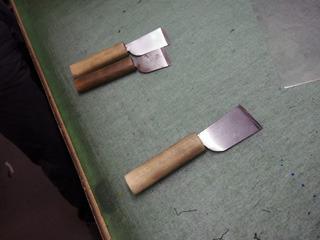 布を切るのに使う裁ち包丁。手前が新品で1年使うと奥の裁ち包丁ぐらいの短さになる。