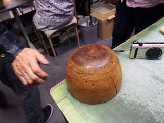 電気で成形する装置ができる前に使っていた木型。かなりの年代物。いまはできあがった帽子を置く台として使用