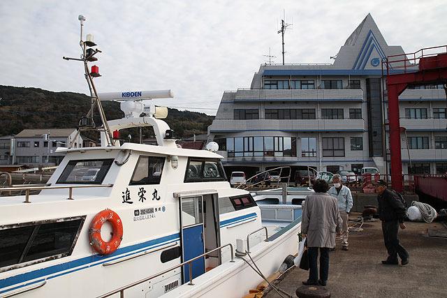 この船に乗って。後ろに見える建物はホテル兼フェリー待合室兼市役所支所。待合室には釣り竿が立てかけてあった。