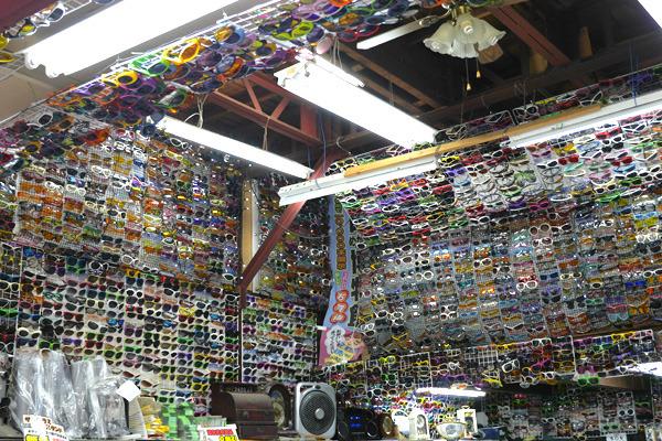壁から天井から、所狭しと貼り付けられたメガネ&サングラス