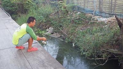 釣り堀の隅で何かを釣って遊ぶ従業員さん。