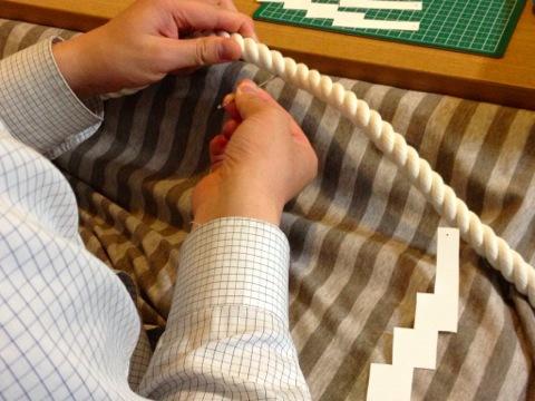 プラスチックの紙垂に穴をあけ、テグスでロープに結びつける