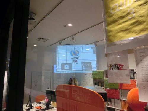 窓際に置いたプロジェクターからロゴを投影する