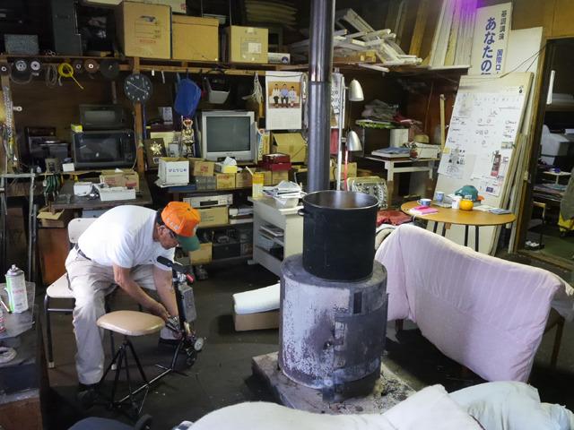三輪車をいじる大西さん。真ん中のストーブでふとんを乾かしている。
