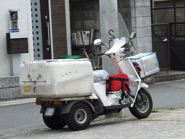 足の置場もないほど積んだ荷物。ハンドル部分にはクリップで留められた書類。限界を超えて仕事をする男の姿そのものである