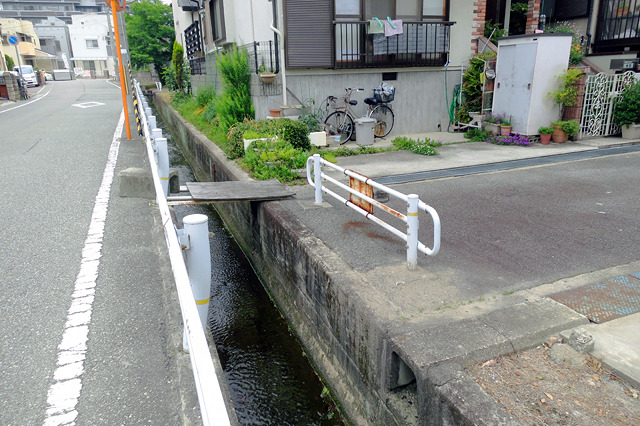 水路で行き止まりの住宅街路地。そこにかけられた「マイ橋」。ガードレールで阻まれている点がいとおしい。側溝に使われるコの字型コンクリートで重しがしてある点もキュート。