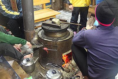 ここの暖房は薪ストーブ。ストーブの上には釜が乗っててお湯沸かしてます。