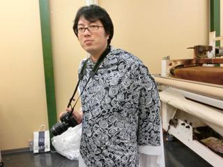 工場でできたての布をまとう西村さん