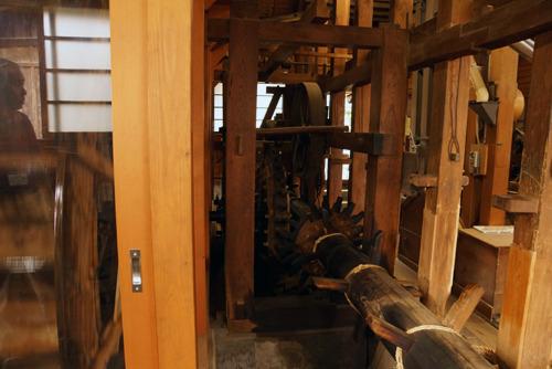 水輪の回転が木製の回転軸や歯車に動力を伝達し…
