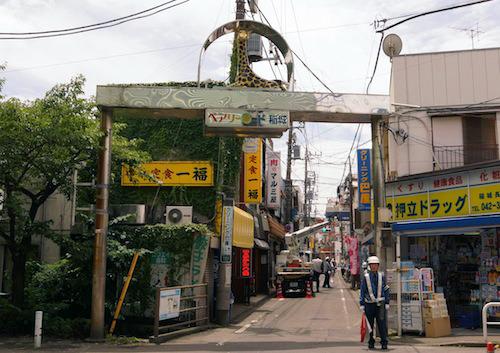 稲城長沼駅商店街のゲート。最上部にキリンという高さのインフレ状態。