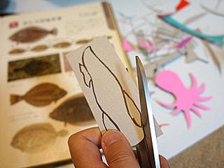 魚のシルエットに厚紙を切り抜いて、おりがみを貼り付けて、と。